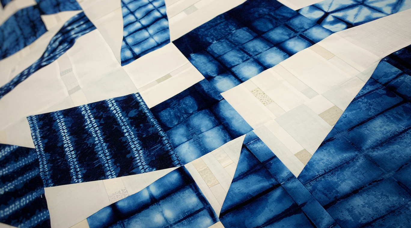modern quilt using shibori indigo dyed cotton with off white linen