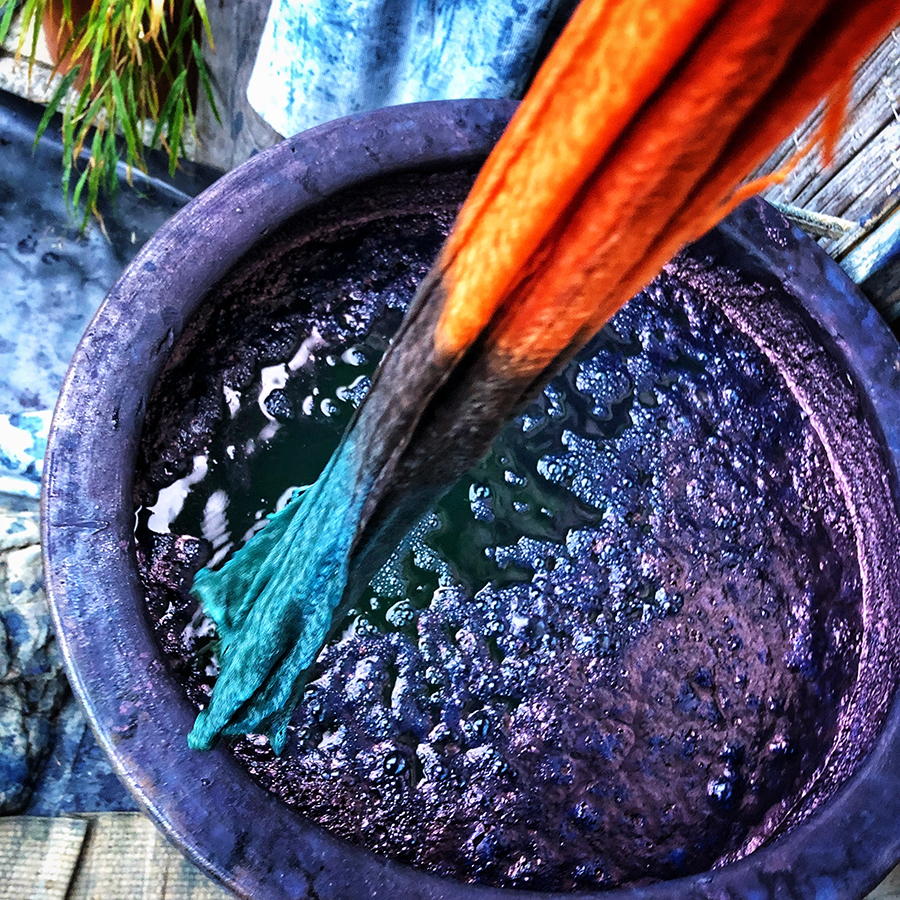 Fabric being dipped into a vat of indigo dye