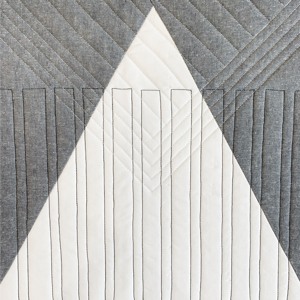 Minimal quilt design with triangle in grey and white