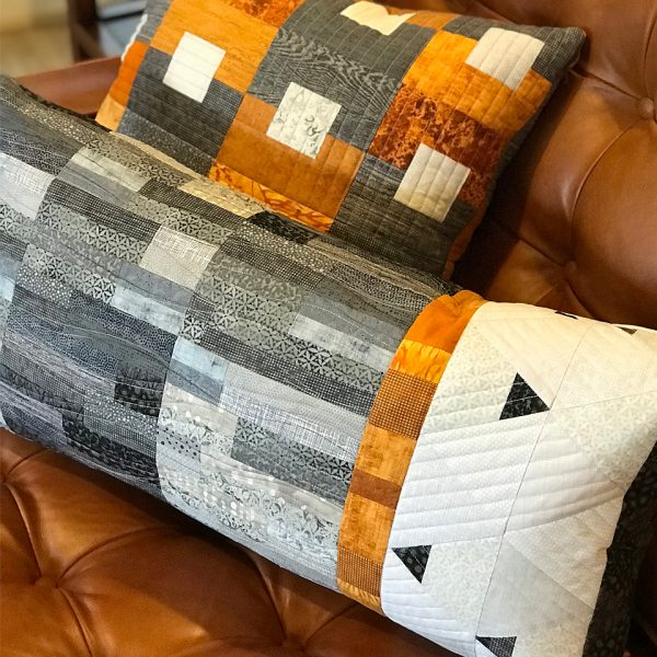 Quilted pillows in grey, rust and white on a rust leather sofa