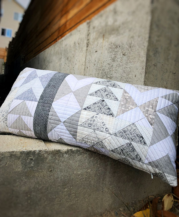 Quilted pillow with modern flying geese design in grey and white
