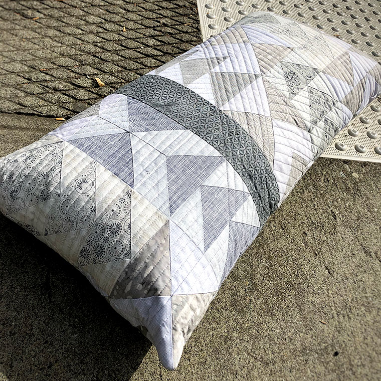 Quilted pillow with modern flying geese blocks in white and grey