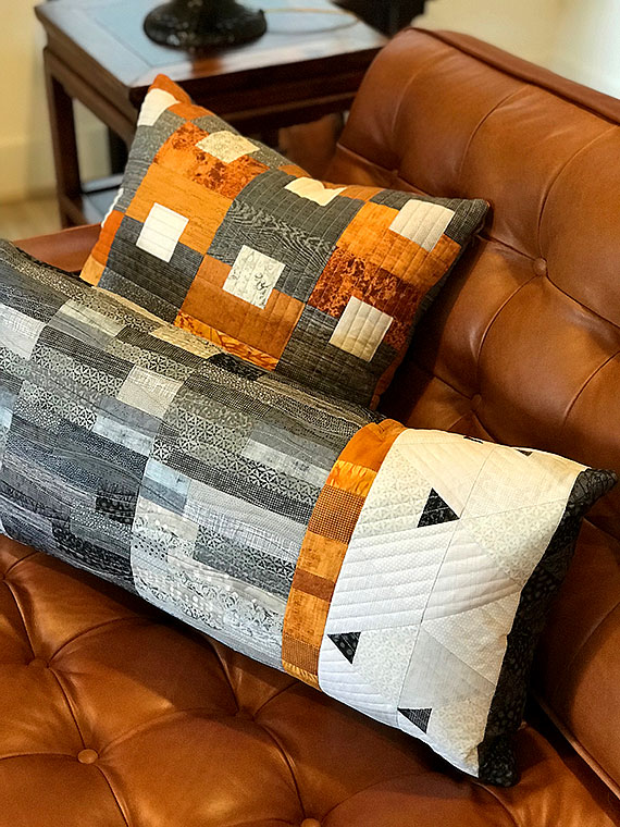 Quilted pillows in rust, grey and white on a rust leather sofa