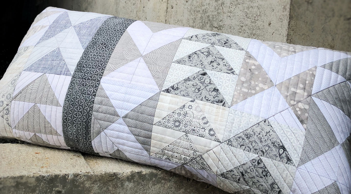 Quilted pillow with modern flying geese blocks in grey and white
