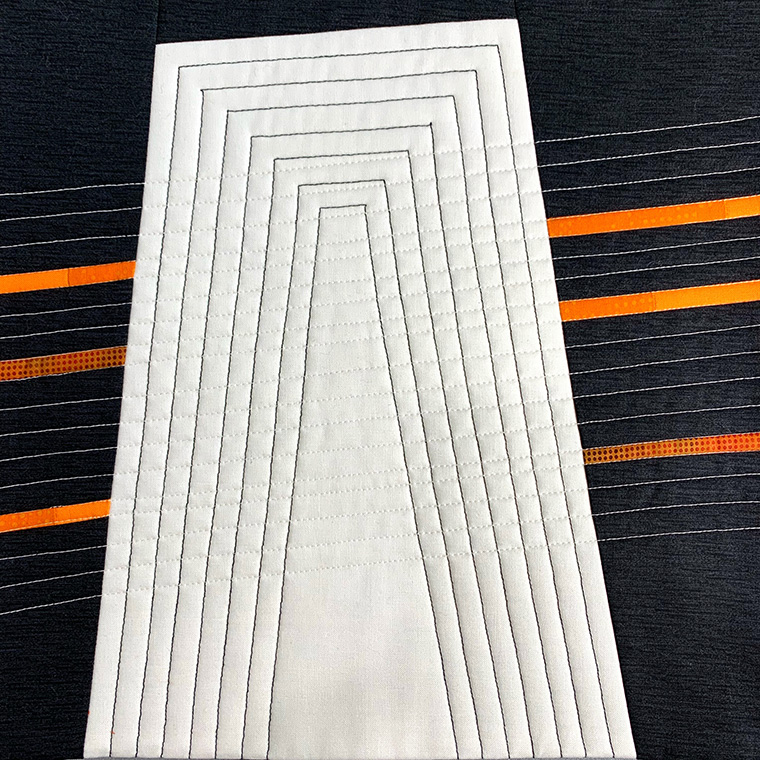 Modern abstract quilt in black and white with orange lines