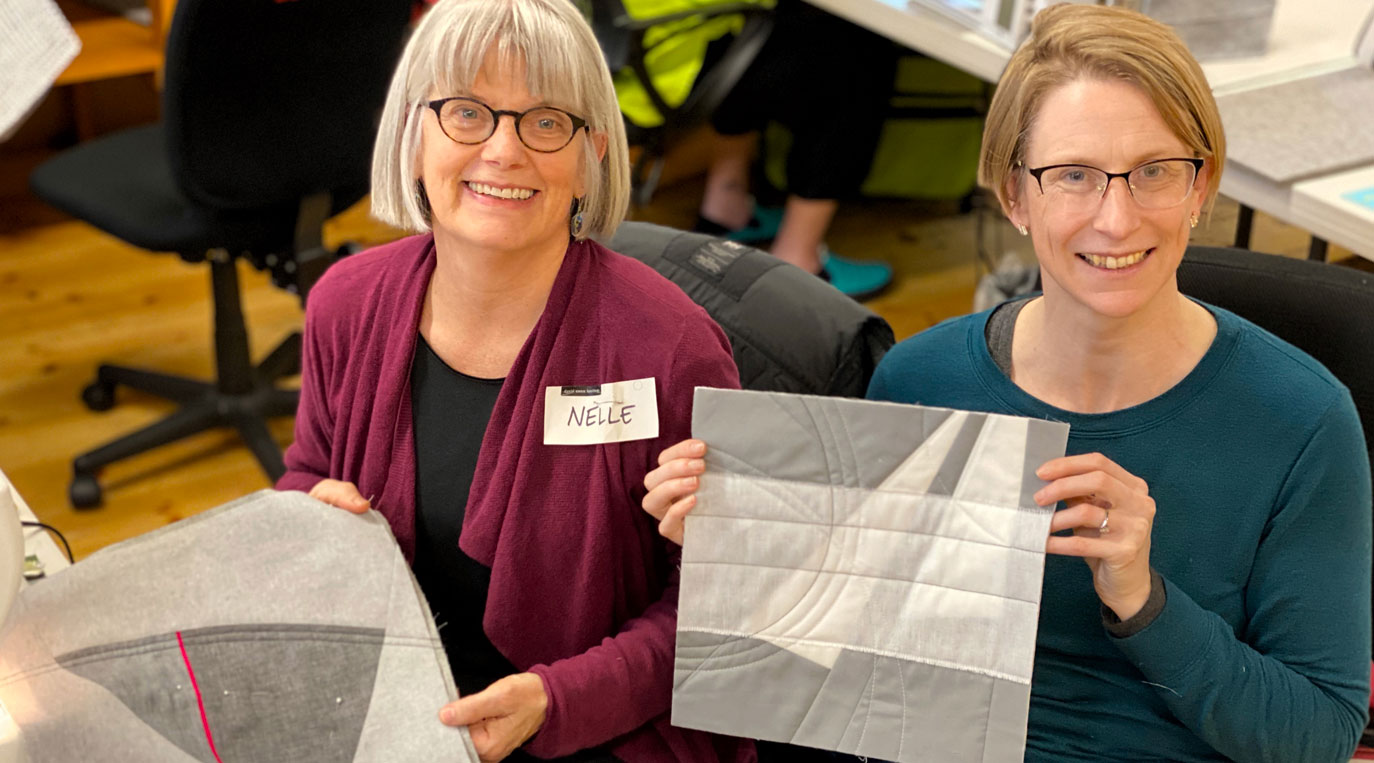 Modern Abstract Quilts Workshop – two students holding their mini fabric quilts