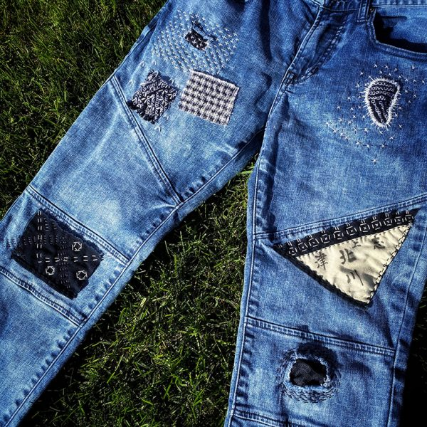Blue jeans lying on grass, patchwork and visible mending